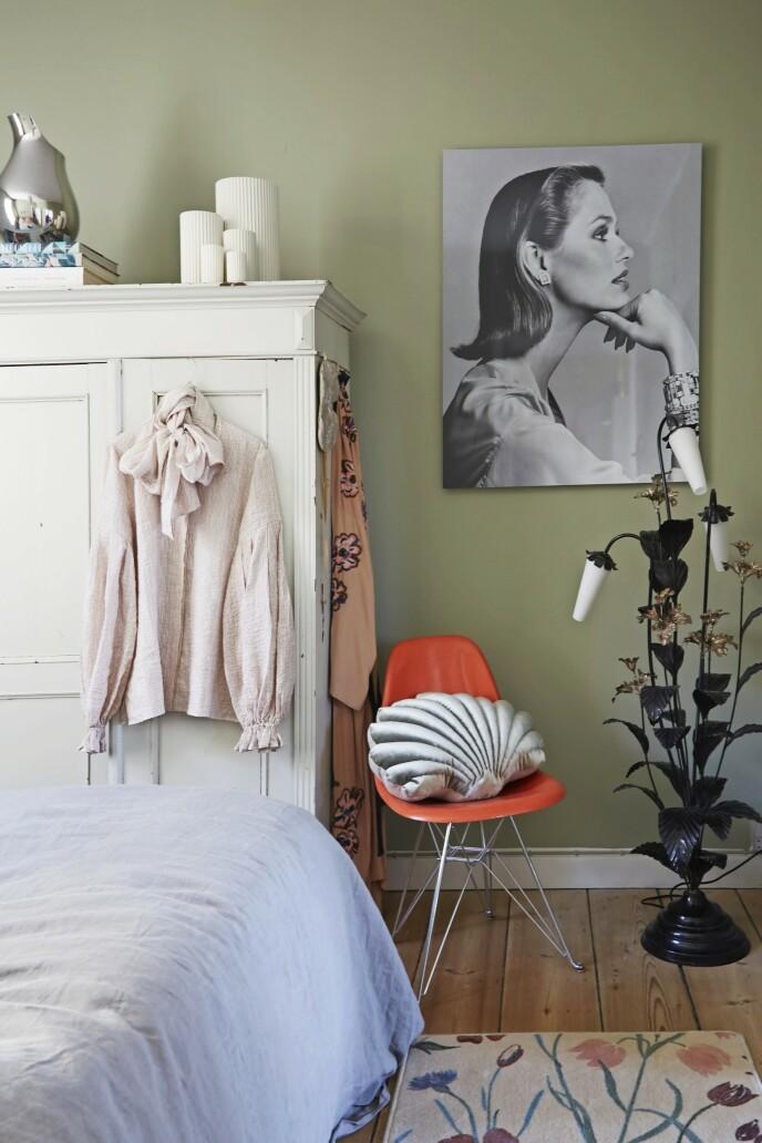 Bettina har skapt en fin stemning i parets soverom med det blomstrete gulvteppet fra Tapet-Cafe, vintagelysestaken fra Fil de Fer og konkylieputen fra Rêve de Renard. Eamesstolen er kjøpt brukt, mens fotografiet er kjøpt hos Privé Copenhagen.