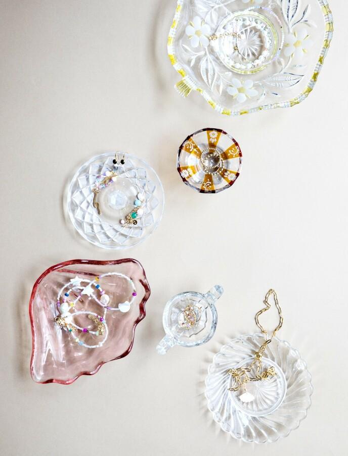 Vintage glasskål med gule blomster og blank skål med lokk (begge fra Instagram-profilen @tussetingfinder). Lite glass med røykfarget mønster og liten blank tallerken (begge fra Shop Dora). Lite glass med hank (Skindergade Antik). Rosa glasskål formet som et skjell (Hay). Smykkene er fra Stine A. FOTO: Pernille Enoch