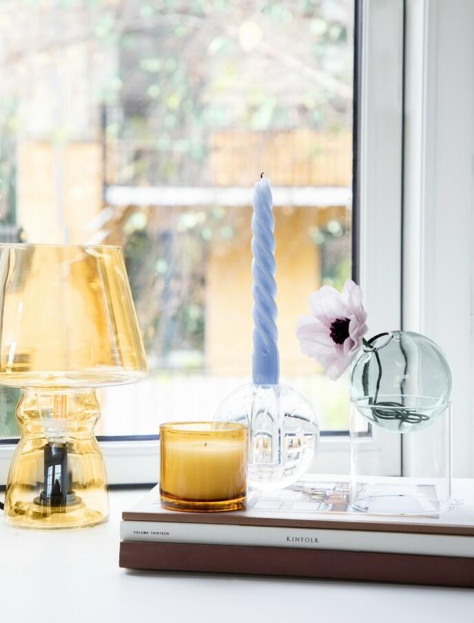 Lampe i gult glass (Notre Dame). Røykfarget glass (@tussetingfinder på Instagram). Rund lysestake (Ferm Living). Bøyd lys (Hay). Rund vase på fot og papirblomst (begge fra Studio About). Tips! Støp ditt eget lys i et farget glass ved å smelte stearin, som anvist på pakken, direkte i glasset. FOTO: Pernille Enoch