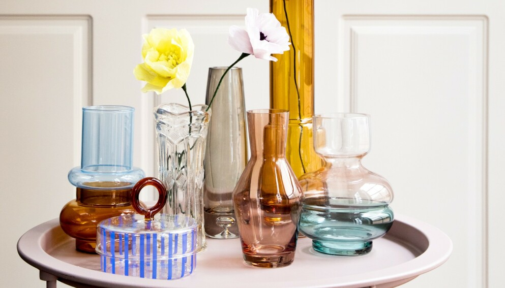 GLASS: Tofarget vase med oransje bunn (Hübsch). Stripete krukke med lokk (Shop Dora). Klar vintagevase (Shop Dora). Grå vase og rosa vase (begge fra Notre Dame). Høy, oransje vase (Ro Collection). Tofarget vase med grønn bunn (Villa Collection). Papirblomster (Studio About). Rundt bord (Jysk). FOTO: Pernille Enoch