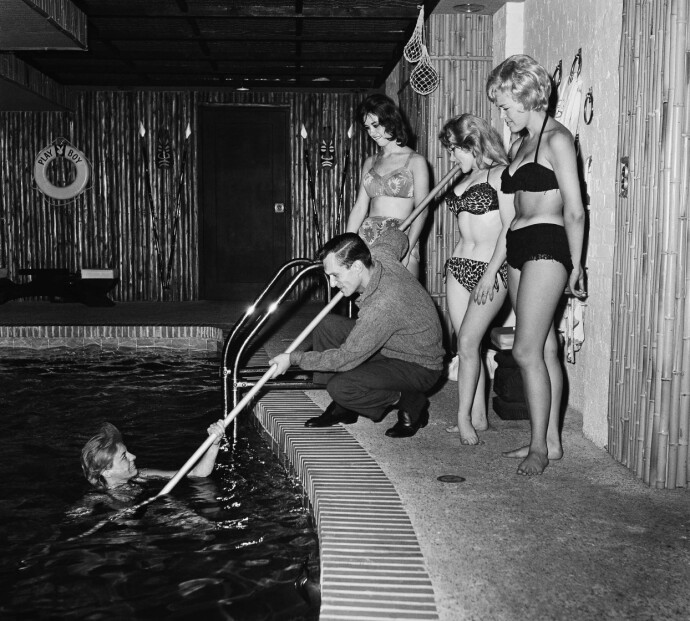 UNG PLAYBOY: Hugh Hefner i kjent stil i leiligheten sin sommeren 1961. Ingen av kvinnene er navngitt. FOTO: NTB