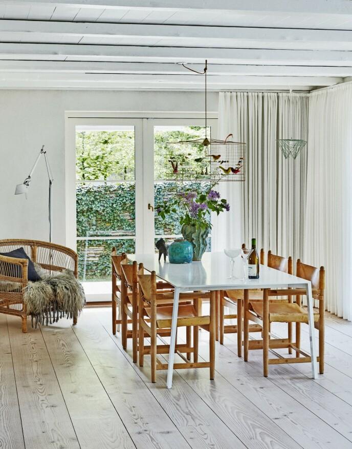 En myk loungestol av bambus gir sammen med gardiner fra gulv til tak en fin atmosfære ved spisebordet. Gulvlampen heter «Tolomeo» og er fra Artemide.