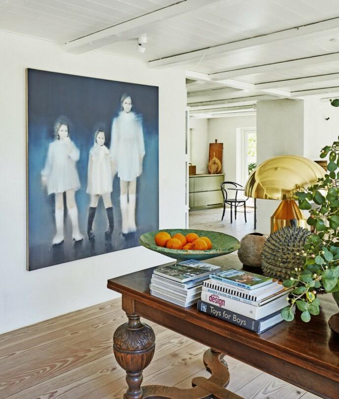 Et stort maleri, som tar opp alle nyansene i hjemmet, har fått plass på veggen ved det gamle bordet. Maleriet er av Siri Gindesgaard.