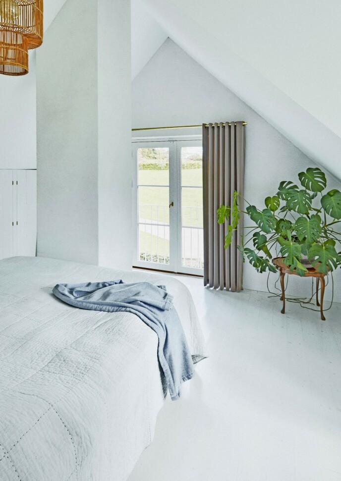 Soverommet er helt enkelt innredet i lyse nyanser, for her er følelsen av ro sentral. De grå gardinene har husets eier selv designet.