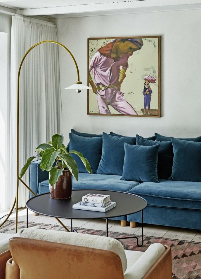 Myk hygge i stuen med velursofa, kelimteppe og grønne planter. «Coco Globe» er navnet på stuebordet som er designet av Caroline Ek, og som blant annet forhandles av royaldesign.no. Maleriet er av Els Cools.