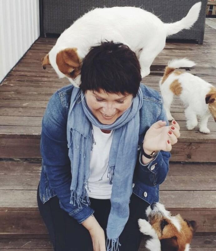 DYREGLAD: Eli er glad i dyr, og en stund lånte hun en liten Jack Russel som ellers bodde på kennel. Her besøker hun kennelen. FOTO: Privat