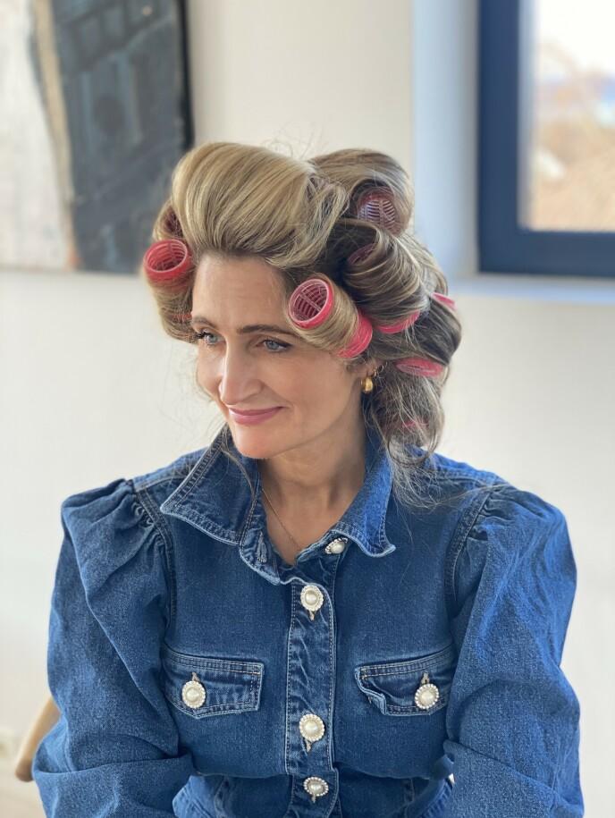MED RULLER: Frisør Siv Oldervik viser hvordan hun fester sine hårruller for å skape looken. Foto: Siv Oldervik