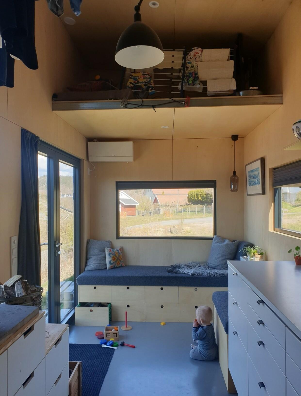 HØYT UNDER TAKET: Den ene hemsen kan brukes som gjesteseng eller til oppbevaring. Store glassdører og vinduer som slipper inn mye lys, får boligen til å virke større. FOTO: Privat