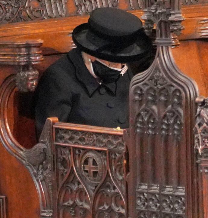 ALENE: Dronning Elizabeth bøyer hodet i sorg etter tapet av ektemannen prins Philip. Grunnet koronarestriksjonene satt dronningen alene på benken i St George's Chapel under begravelsen. FOTO: NTB