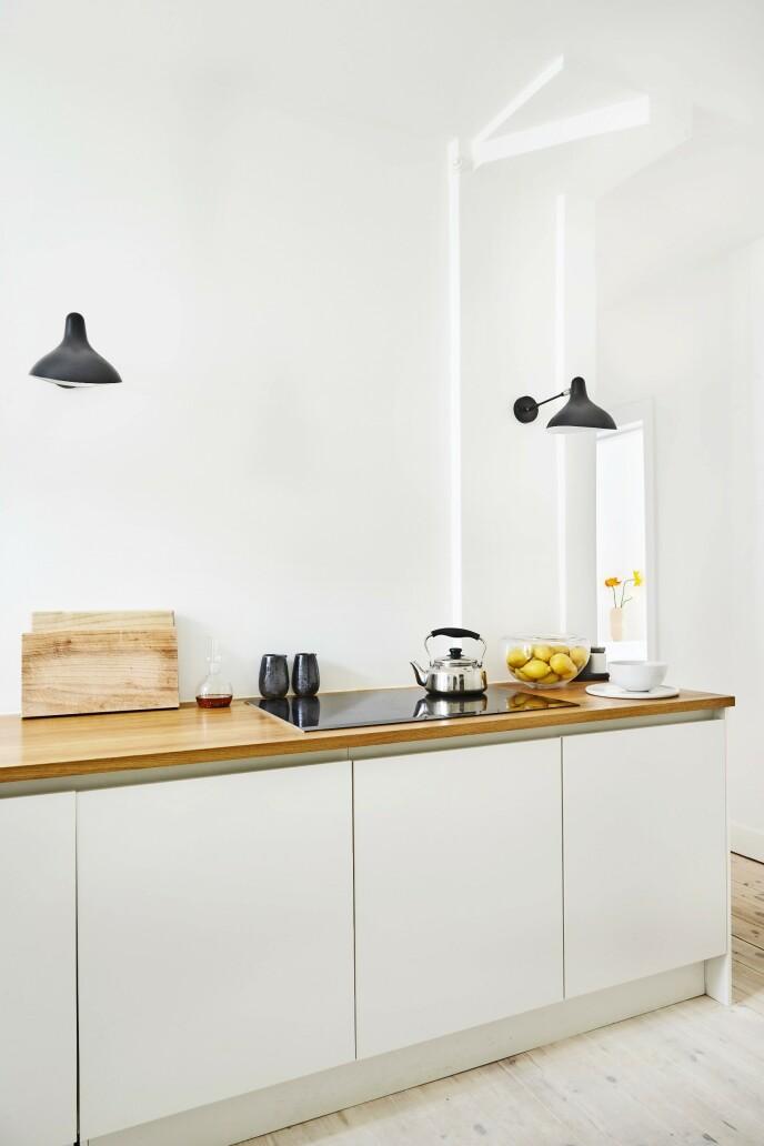 Mette og Rasmus har valgt et lyst og enkelt kjøkken med noen ekstra stilige detaljer, slik som «BS5»-lampene. Tips! Har du et hvitt kjøkken, kan du myke opp inntrykket ved å ha en benkeplate i varmt treverk.