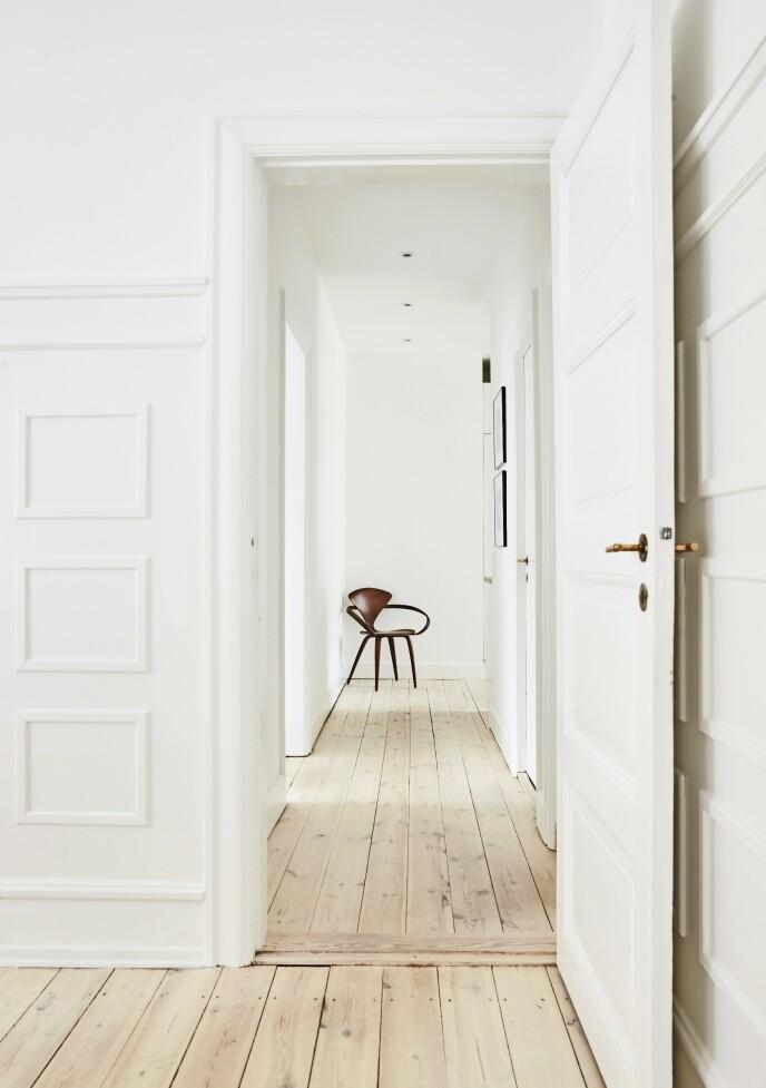 Stolen i gangen er fra Norman Cherner og ble designet i 1958. I 1961 malte Norman Rockwell stolen som en del av maleriet «The Artist at Work», og i den forbindelse ble stolen for alvor anerkjent i USA. Tips! Skap blikkfang i en hvit, lang gang med et skulpturelt møbel.