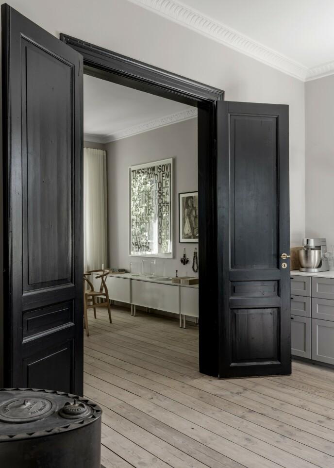 Kontrastfarger er en sikker vinner, og her er dørkarmen og selve døren mellom kjøkkenet og spisestuen blitt malt svart. Det markerer tydelig at det er en oppdeling av rommet, selv om det er åpen forbindelse mellom de to rommene.