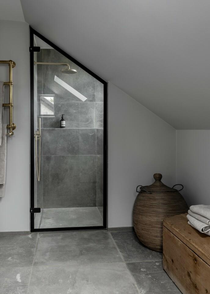 Badet er holdt i grå toner med varme innslag av naturlig treverk og messing. Tips! Ved å velge armatur i messing får du varme inn i rommet, og det gir et fint motspill til de grå flisene.