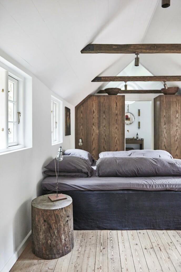 Nattbordet er laget av en rå trestubbe. Lampen er et funn fra Frankrike, og sengetøyet er fra Himla. Tips! Grå og brune nyanser gir en varm og rolig stemning på soverommet.