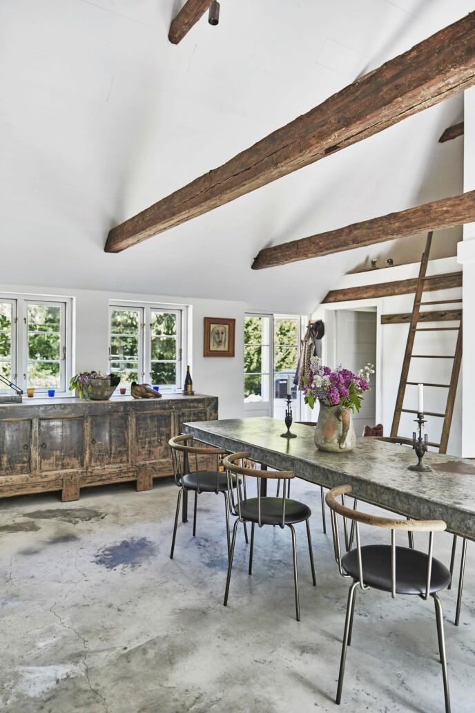 Gulvet på kjøkkenet er i betong. Det står i skarp kontrast til husets yndige ytre, men det passer bra sammen med stolene av svartoljet eik, det rå betongbordet og den gamle skjenken. Spisebordet er funnet i Frankrike, og stolene er fra Eberhart Furniture. Skjenken er fra Rosmosegaard.