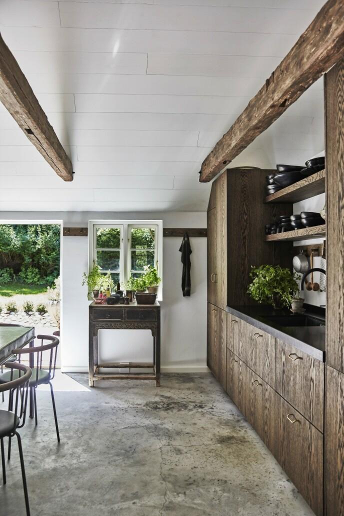 Det vakre, mørke kjøkkenet er fra Vivre, og virker lett på grunn av de åpne hyllene. Her står hele samlingen av mørkt servise framme og ser skulpturelt ut. Fra kjøkkenet er det utgang til en spiseplass i det fri. Krydderurter gror i potter på det lille bordet ved døren, så de er innen armlengdes avstand.