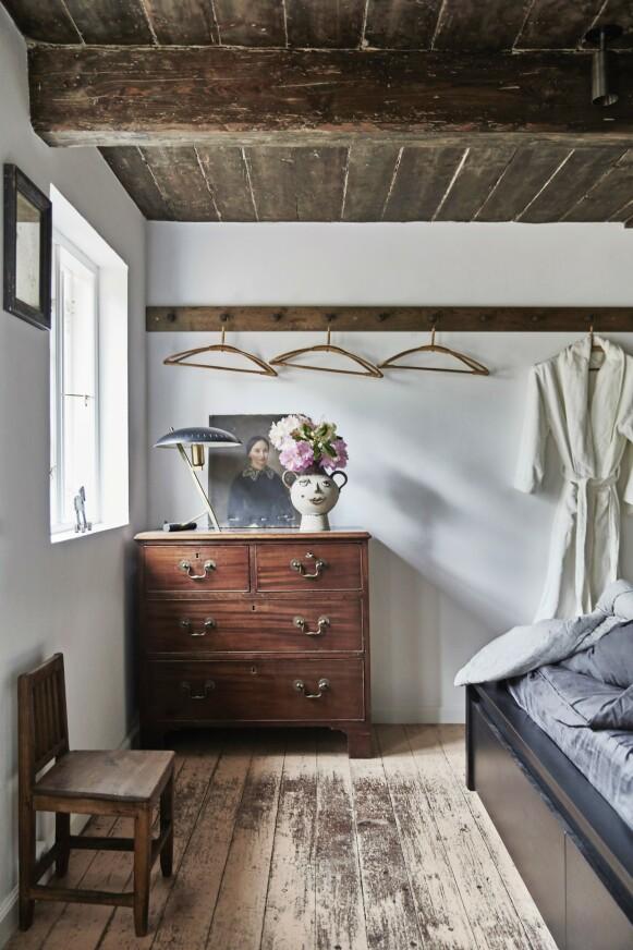 Dette soverommet er helt enkelt innredet. Det bidrar til at det vakre, mørke taket, den enkle knaggrekken, den gamle stolen og den fine kommoden får oppmerksomheten. Bambuskleshengerne er fra loppemarked.