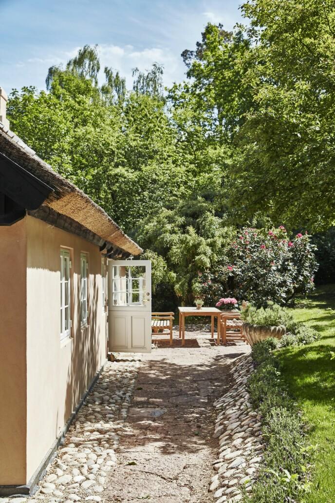 Hagen rundt det nostalgiske huset er frodig, litt vill og naturlig, for slik synes eierne at en skikkelig sommerhushage skal være.