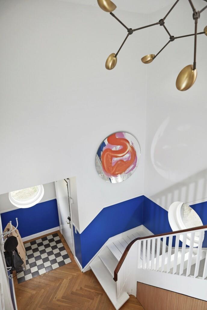 Den blå fargen i gangen har Trine valgt for å skape en gledelig velkomst. Den fortsetter langs den originale trappen opp til andre etasje. Flisene ved hoveddøren er originale. Knaggrekken «Tree Wall» er fra Fritz Hansen.