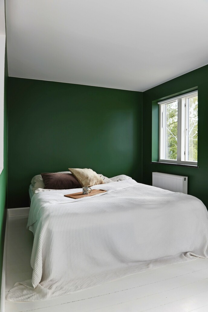Den flaskegrønne fargen omkranser sengen og skaper en beroligende ramme. Sengeteppet er fra Ikea, og koppen er fra The Clay Play Tips! Velg farger etter hvilken stemning du ønsker, f.eks. en dynamisk blåfarge i entreen og en rolig mørkegrønn på soverommet.