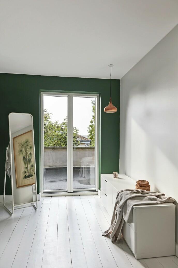 For roens skyld bør ikke kontrastene være for store på soverommet, så her er veggene malt i en dyp nyanse av grønt. Kobberlampen er fra husets tidligere eier. Speil og kommode er fra Ikea.
