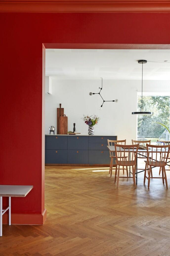 Farger kan brukes til å ramme inn utsikten fra et rom til et annet, som her mellom den røde og oransje stuen og kjøkkenallrommet med blågrå fronter. Tips! Lek med sterke farger som gir kontrast. De må ikke harmonere for å gi et spennende resultat.