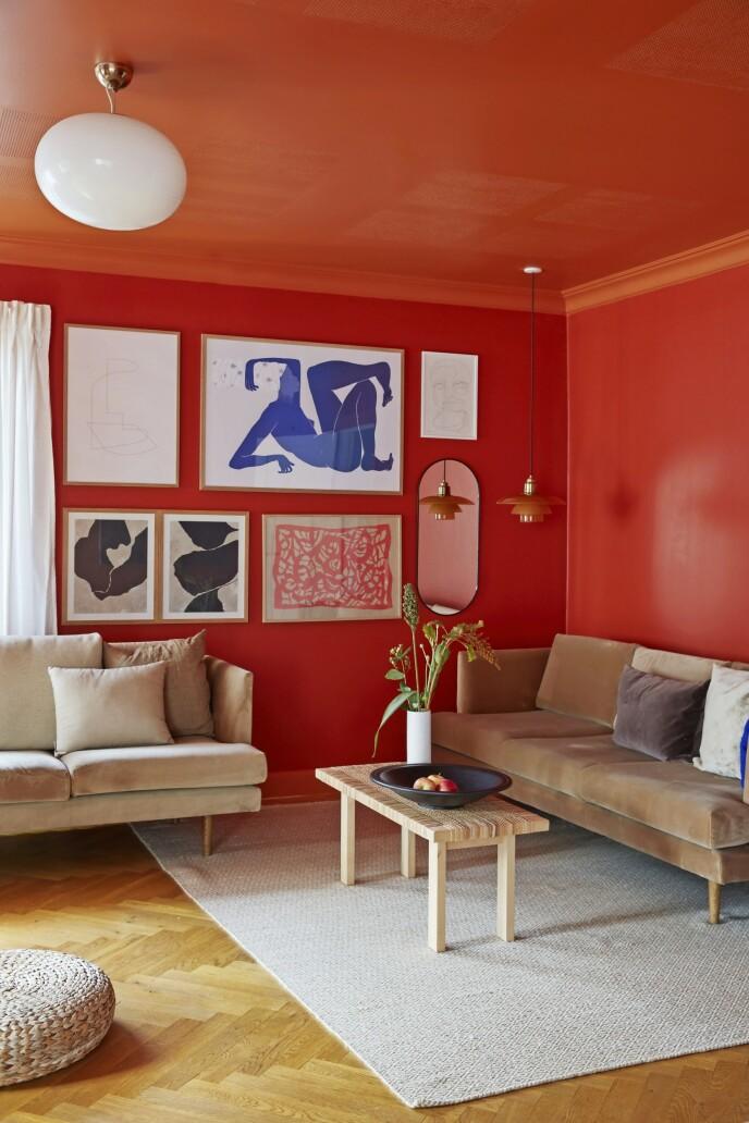 Det modigste valget av farger er gjort i stuen. Her har Trine malt tak og vegger i rødt og oransje, farger som hun selv har blandet. Bildene er blant annet fra Hein Studio, Mama og Henri Matisse. Gulvteppet er fra Ellos, flettet benk fra Ikea og sofaer fra Sofacompany.