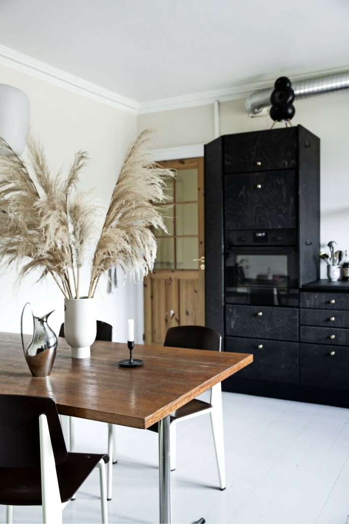 Også spisebordet er kjøpt brukt, mens de strømlinjede stolene er Lines dyreste investering. De er fra Prouvé/Vitra. Vase fra H&M Home og kanne fra George Jensen. Veggfargen heter NCS 1005-Y20R.