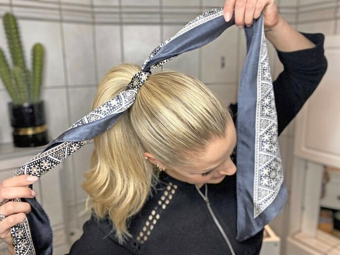 2. Gre håret, og lag en høy hestehale. Bruk litt hårspray for å få ekstra hold. Knyt silkeskjerfet rundt hårstrikken. La det være like mye silkeskjerf på hver side av knuten.