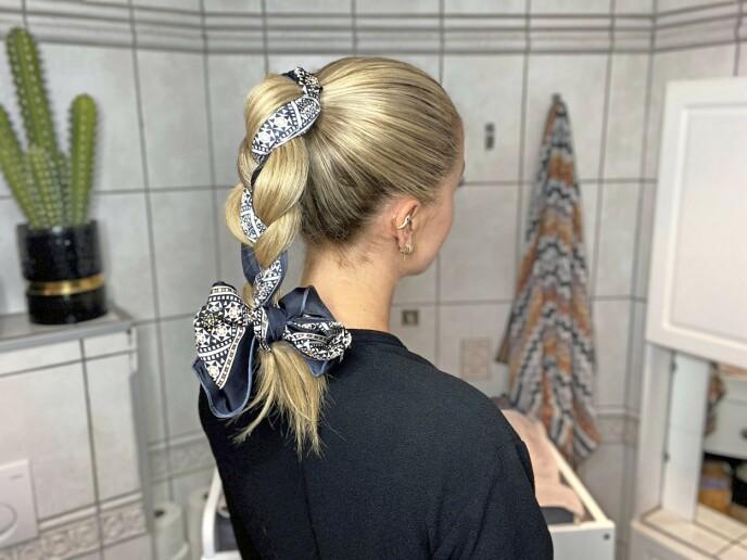4. Fest fletten med en hårstrikk. Knyt en sløyfe med endene av silkeskjerfet for å skjule hårstrikken.