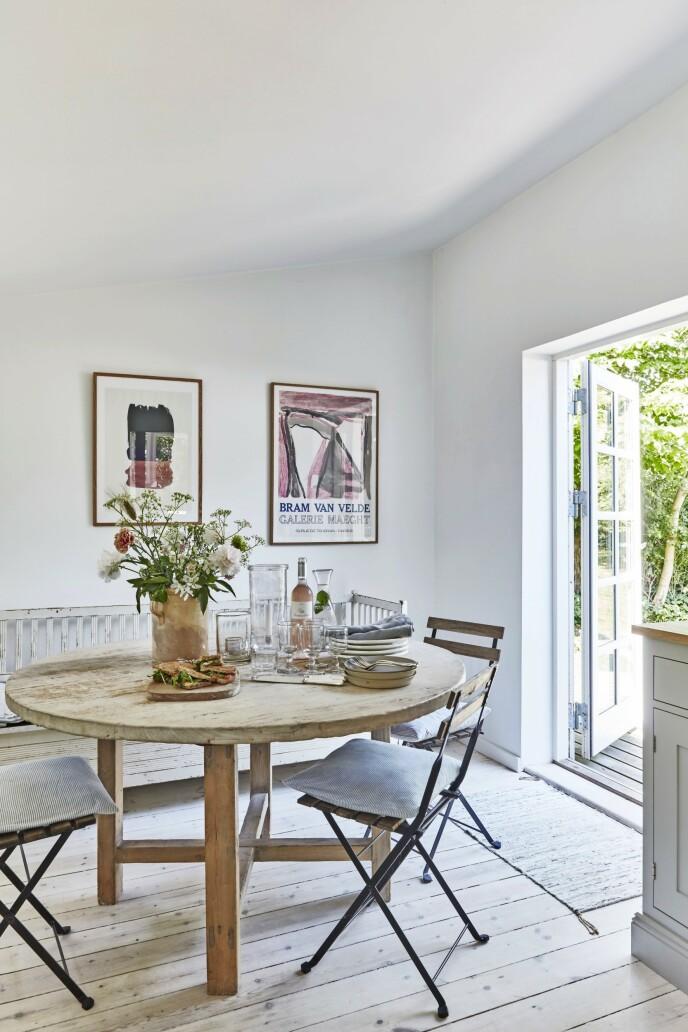Stolene rundt spisebordet på kjøkkenet er samme modell som dem rundt terrassebordet. Det bidrar til å skape sammenheng mellom inne og ute, og det gjør det mulig å supplere med stoler hvis det kommer gjester, uten at det blir en spraglete miks av stoler. Bare sørg for at treet og overflatebehandlingen tåler vær og vind. Spisebordet er fra Rosmosegård, og stolenes trekk er sydd av tekstil fra Skjalm P. Den gamle, hvite slagbenken er kjøpt brukt, og bildene er gamle museumsplakater.