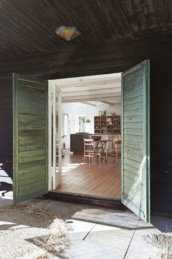 Gulvene i sommerhuset står umalte opp mot det øvrige hvite treverket, og det gir et varmt fundament for alle hjemmets tremøbler.
