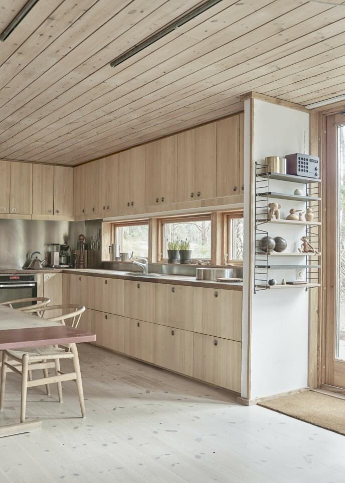 På veggen henger en «String Pocky»-hylle. I det lyse kjøkkenet står Hans Wegners «Y-stoler» rundt spisebordet.