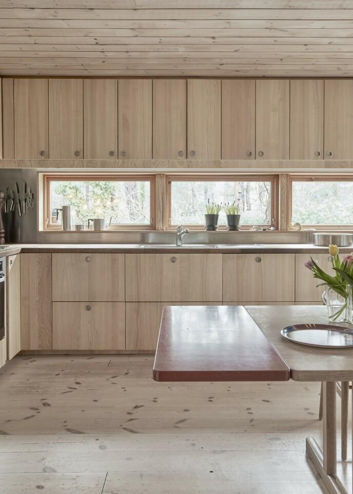 Både gulv, tak, kjøkkenfronter og spisebordet er i lyst tre. Og for å bryte er det satt en plate i bordet i en annen nyanse. Det gir motspill og litt «edge».