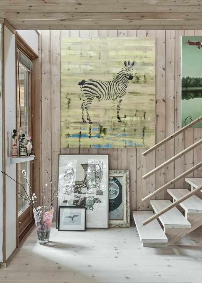 Forskjellig kunst henger på veggen ved trappen. Og på gulvet står det også et litt tilfeldig utvalg bilder.