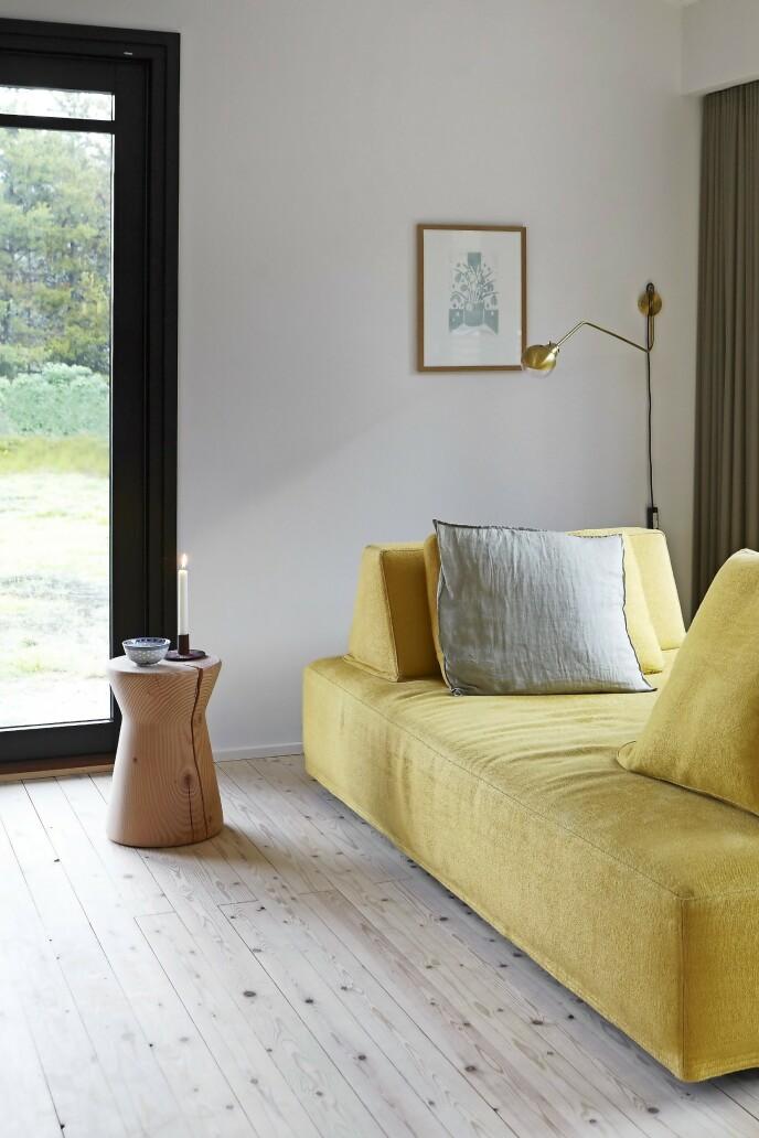 Den gule sofaen fra Eilersen har fleksible ryggdeler som kan flyttes rundt, så de ikke stenger for utsikten mot hagen.