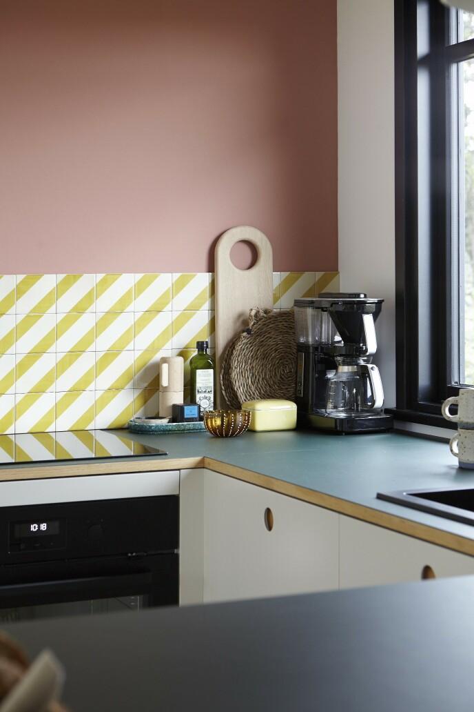Kjøkkenet med malte fronter og en benkeplate av grønn linoleum satt på finer er fra Reform. Mette har valgt de hvite og gule flisene fordi nyansen harmonerer med den gule sofaen i rommets stuedel. Flisene er fra File under Pop. Det samme er den røde malingen som tilfører varme til kjøkkendelen.