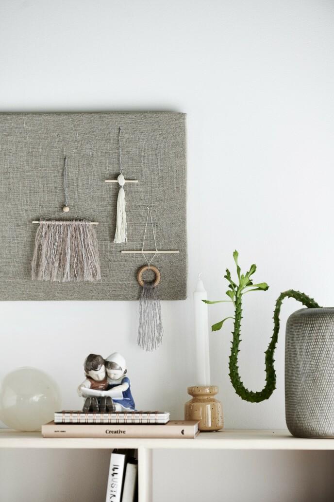 Små uroer eller dusker laget av trepinner, trekuler og garn fra Søstrene Grene. På benken står blant annet en hvit kule i selenitt fra Tine K. Home, en porselensfigur fra Bing & Grøndahl og en lysestake fra Bloomingville.