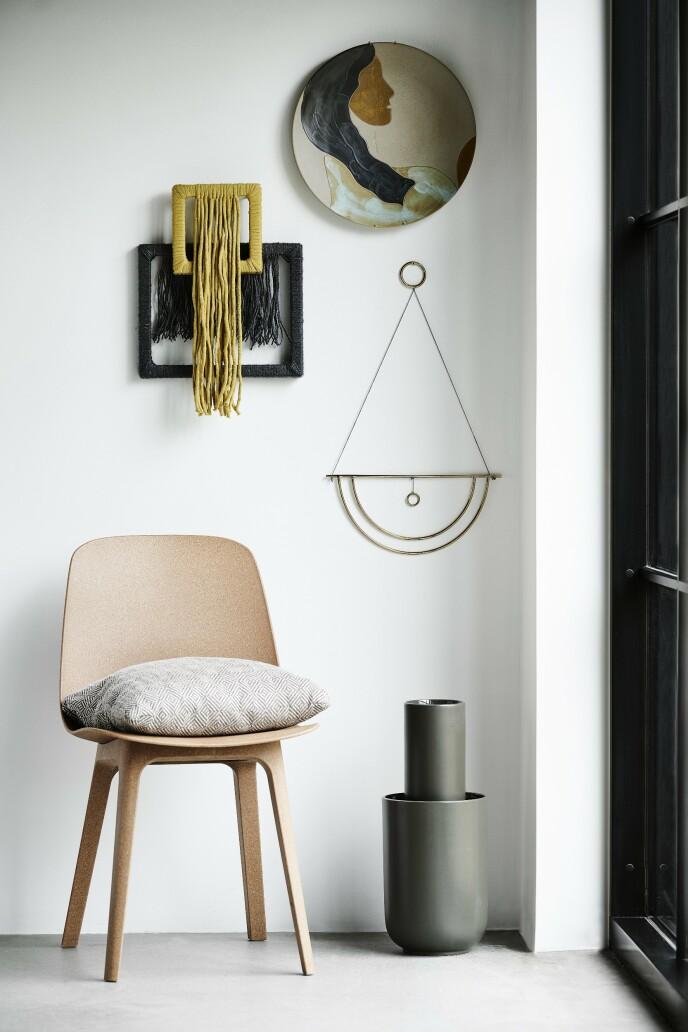 Trerammer og garn i gult og svart fra Søstrene Grene. Keramikkplaten på veggen er fra Ferm Living. Veggdekorasjonen i metall er fra Bloomingville, og stolen er fra Ikea. Puten og gulvvasen er fra Woud.