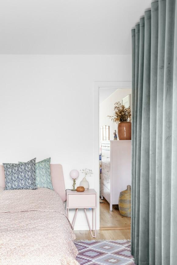 Den rosa fargen som er blitt brukt på veggen andre steder i leiligheten, blir på soverommet tatt opp igjen på nattbord, sengeteppe og sengegavlen.