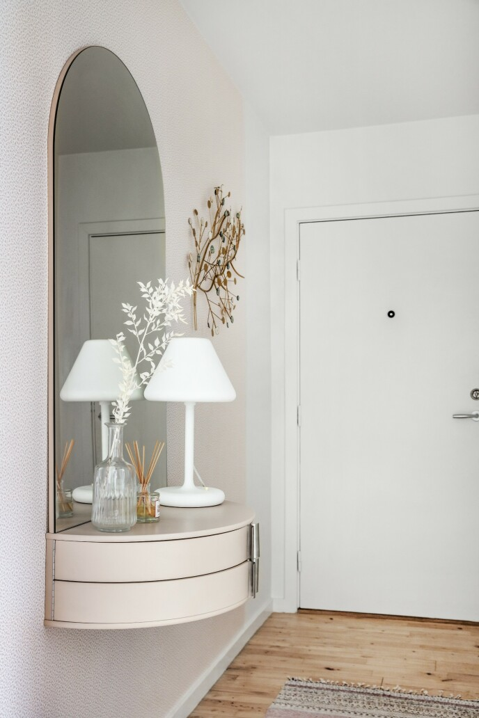 I gangen blir man møtt av et elegant speilmøbel.