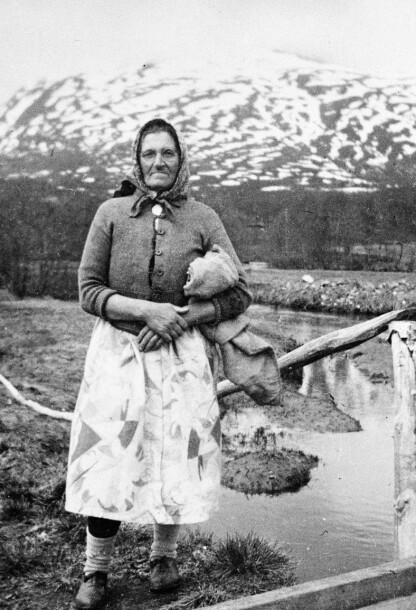 TETT PÅ: En bondekone på en gråd hvor den norske hæren hadde mitraljøseleir på låven under kampene om Narvik. Hun fikk tillatelse av de militære lederne til å krype gjennom skyttergraver for å melke kuene på den samme låven. FOTO: NTB