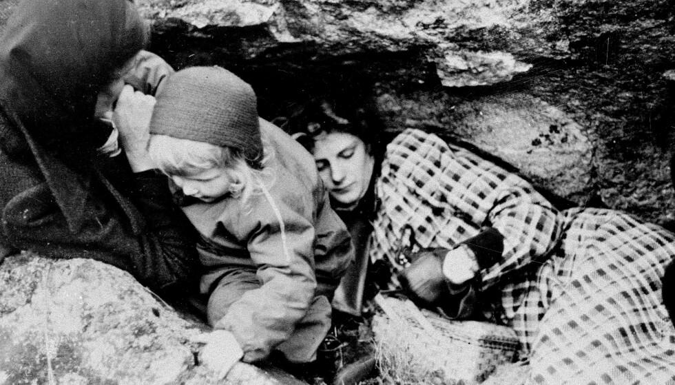 I SKJUL: Tre generasjoner i skjul under tysk flyangrep i Narvik 1. juni 1940. Innbyggerne rømte byen under flyangrepet og gjemte seg i fjellsprekker og huler. FOTO: NTB