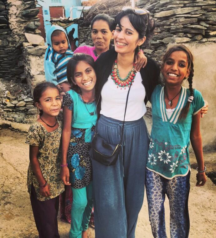 RØTTER: Iram på en av sine mange reiser til India, som var farens hjemland. Her i Rajastan, sammen med barn fra landsbyen. FOTO: Privat