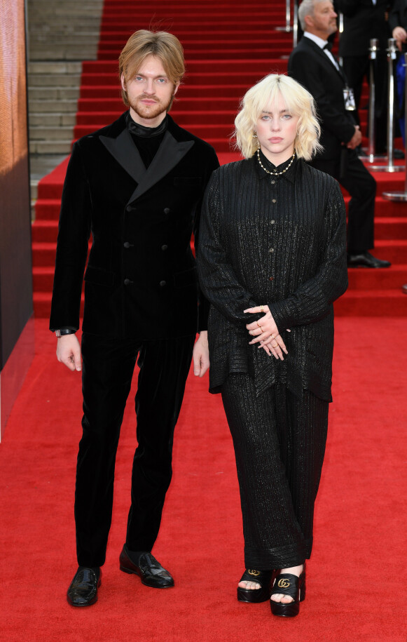 Billie Eilish og broren Finneas O'Connell. Hun fra topp til tå i Gucci og han i en svart dress i fløyel fra Armani og klokke fra Cartier. De to står bak soundtracket til den nye Bond-filmen. FOTO: NTB