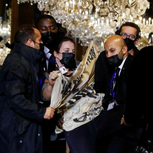 BÆRES VEKK: Her bæres en aktivist vekk fra Louis Vuitton-catwalken i Paris. FOTO: NTB