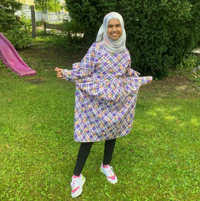 GLADJENTE: Zenab liker å bruke stoffer fra bruktbutikker når hun syr klær. Da blir det mange fargesterke mønstre, som gjenspeiler det gode humøret hennes. Foto: Privat.